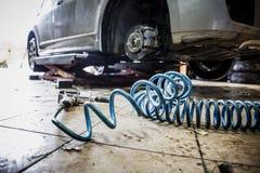 Bil i garage i för reparationsservice för auto mekaniker seminarium med den speciala maskinen som reparerar utrustning - pneumati royaltyfri bild
