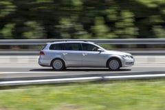 Bil i snabb rörelse med att panorera effekt på huvudvägen royaltyfria bilder