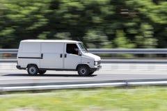 Bil i snabb rörelse med att panorera effekt på huvudvägen arkivfoton