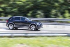Bil i snabb rörelse med att panorera effekt på huvudvägen arkivbild