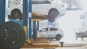Bil i tjänste- lyfta för automatisk för att reparera, mekaniker i garage fotografering för bildbyråer
