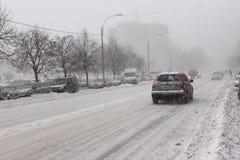 Bil i trafik på häftig snöstorm fotografering för bildbyråer