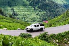 Bil med amerikanska flaggan i glaciärnationalparken, USA Royaltyfri Fotografi