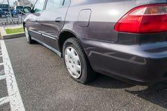 Bil med ett plant gummihjul på en asfaltparkeringsplats royaltyfri fotografi