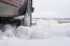 Bil med monterade snökedjor i vintrig miljö Royaltyfri Fotografi