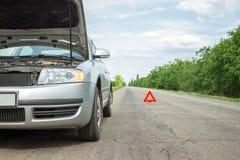 Bil med problem och en röd triangel som varnar andra väganvändare Royaltyfri Fotografi