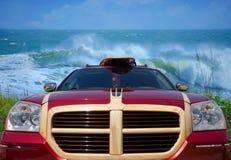 Bil med surfingbrädan på stranden med stora vågor Royaltyfri Foto