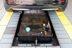 Bil och kontrollgrop i garaget, grop för bilreparationsmitt arkivbild