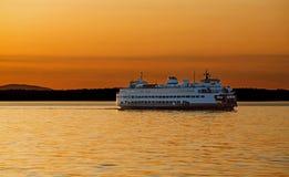 Bil- och passageraretransportfärjan tände i guld- glöd på solnedgången Royaltyfri Bild