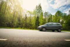 Bil på asfaltvägen i härlig vårdag arkivfoto
