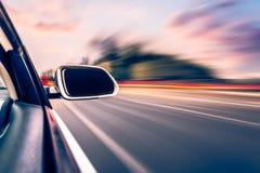 Bil på bakgrunden för suddighet för vägwhitrörelse Arkivbild