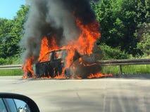 Bil på brand på motorwayen Royaltyfria Bilder