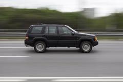 Bil på den hög hastigheten som rusar vägen Arkivbilder