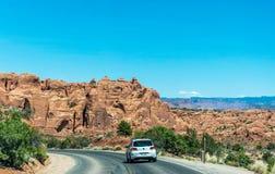 Bil på den moderna huvudvägen i bågar nationalpark, Utah, USA Sommartur till de naturliga dragningarna av Amerika arkivbild