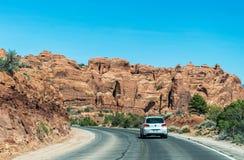 Bil på den nya huvudvägen i bågar nationalpark, Utah, USA Sommartur till de naturliga dragningarna av Amerika arkivfoton