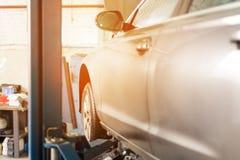 Bil på den tjänste- mitten Medel som lyfts på en elevator Kontroll upp, underhålls- och reparationsbegrepp arkivbilder