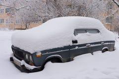 Bil på en gata som täckas med det stora snölagret efter tungt snöfall Extrem häftig snöstormefterdyning arkivbild