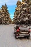 Bil på en snöig väg i vinterskog Arkivbilder
