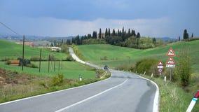 Bil på en väg till och med de tuscanian kullarna stock video