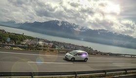 Bil på huvudvägen, bergen och sjöarna Arkivfoto