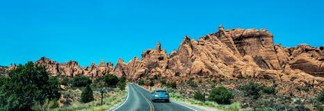 Bil på huvudvägen i bågar nationalpark, Utah, USA Sommartur till de naturliga dragningarna av Amerika arkivfoton