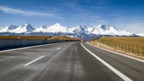 Bil på huvudvägen och Tatra berg, Slovakien arkivbild