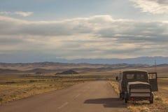 Bil på sidan av en öde väg Arkivfoto