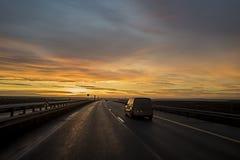 Bil på solnedgångvägen Royaltyfri Fotografi