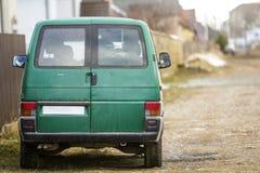 Bil på stadsgatan Grön minibuss som parkeras på sidan av vägen arkivfoto