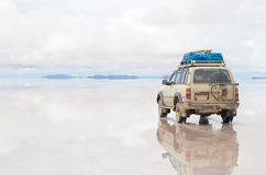 Bil på Uyunien Salar i Bolivia Arkivfoto