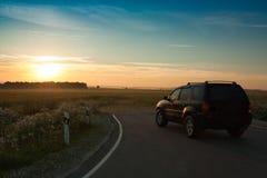 Bil på vägen under himmel med solnedgång av solen Royaltyfri Bild