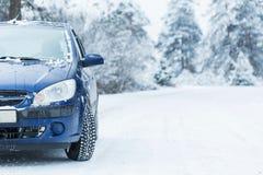 Bil på vintervägen med skogen i bakgrund arkivfoton