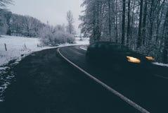 Bil på vintervägen till och med skog Arkivbilder