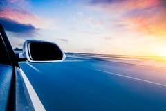 Bil på bakgrunden för suddighet för vägwhitrörelse Arkivfoto