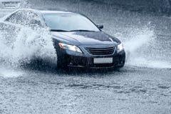 Bil på den våta vägen Arkivfoto