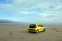 Bil på en öde strand. Arkivfoton