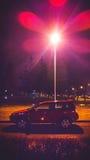Bil på nattetid i en gata Arkivbild