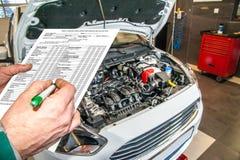 Bil som är diagnostisk och kontrollerar den olje- nivån i motorn i bilservicen Royaltyfri Bild