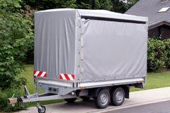 Bil som är traile med den höga gråa tarpen Arkivbild