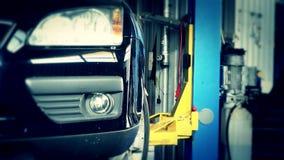 Bil som fäller ned på hisselevator i garage för auto reparation arkivfilmer