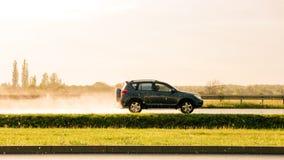 Bil som går snabb på att regna landskap royaltyfria foton