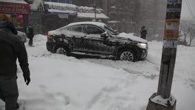 Bil som klibbas i snö under häftiga snöstormen Jonas lager videofilmer