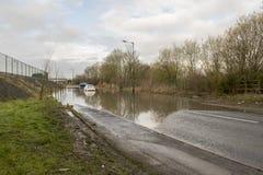Bil som klibbas i vatten på den Dearne vägen efter floden Dearne som översvämmas på Arkivfoto