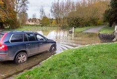 Bil som korsar djup vadställe i Shilton Oxford Royaltyfri Foto
