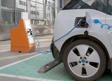 bil som laddar den elektriska stationen Stäng sig upp av strömförsörjningen som pluggas in i ett auto som laddas Royaltyfri Fotografi