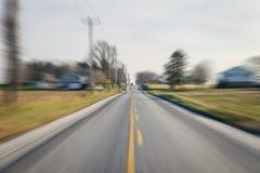 Bil som ner kommer vägen, med mycket rörelse och hastighet som swooshing in mot den royaltyfri fotografi