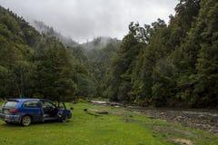 Bil som parkeras i filmiskt landskap, med dimmiga berg, skogen och floden arkivfoto