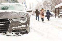 Bil som parkeras i snödriva på stadsgatan Tungt vintersnöfall Folk som går medan stark snö och vind Stormhäftig snöstorm arkivbild