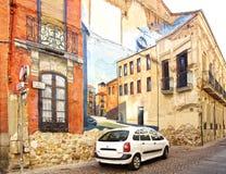 Bil som parkeras längs en kulör fasad med gatakonstväggmålningen Arkivfoto