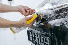 Bil som slår in specialisten som sätter den vinylfolie eller filmen på bilen Skyddande film Applicera en skyddande film med hjälp royaltyfri fotografi